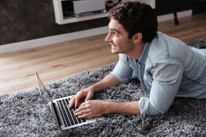 Close up portrait of a man using laptop while lying on carpet at home