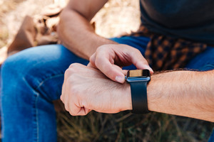 Close up portrait of a man using smartwatch while sitting outdoors
