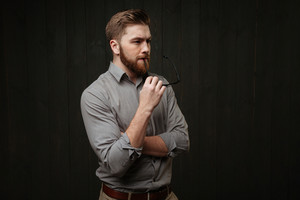 Close up portrait of a pensive bearded man in shirt holding eyeglasses and looking away isolated on the black wooden background