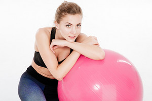 Close up portrait of a pretty sports woman relaxing on pink fitness ball isolated on white background