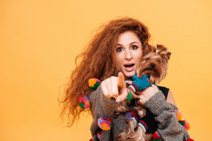 Close up portrait of a pretty young woman holding a dog and pointing finger at camera isolated on orange background