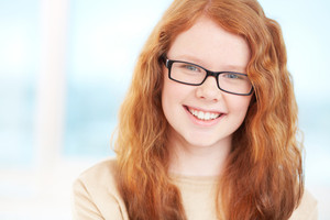 Close-up portrait of a redhead teen in a good mood