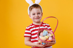 Close up portrait of a satisfied little kid wearing bunny ears and holding easter basket full of colorful eggs isolated over orange background