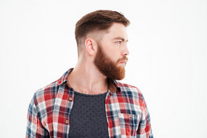 Close up portrait of a serious bearded man in plaid shirt looking away over white background