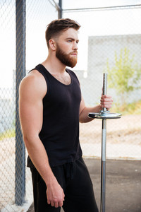 Close up portrait of a serious bearded sportsman holding barbell while standing outdoors
