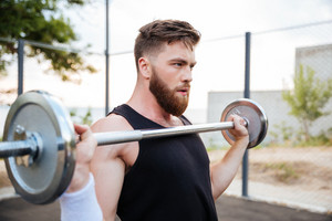 Close up portrait of a serious young man athlete standing and holding barbell outdoors