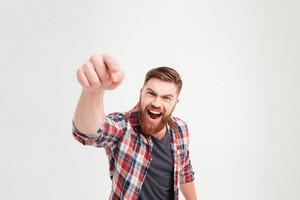 Close up portrait of a shouting casual bearded man pointing finger a camera isolated on a white background