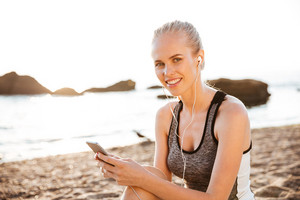 Close up portrait of a smiling blonde sports woman with earphones sitting on beach