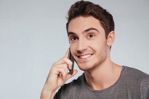 Close up portrait of a smiling handsome man talking on cell phone isolated on the white background