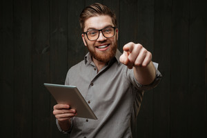 Close up portrait of a smiling happy man in eyeglasses holding tablet computer and pointing at camera isolated on a black wooden background
