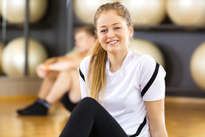 Close-up portrait of a smiling woman at fitness center