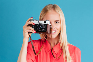 Close up portrait of a smiling young blonde girl holding photo camera over blue background