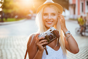 Close up portrait of a smiling young blonde girl holding retro camera outdoors