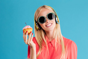 Close up portrait of a smiling young blonde woman in sunglasses listening music with headphones over blue background