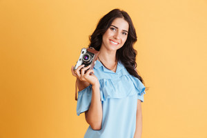 Close up portrait of a smiling young brunette girl holding photo camera isolated on a orange background
