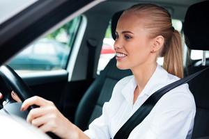 Close up portrait of a smiling young business woman driving her car