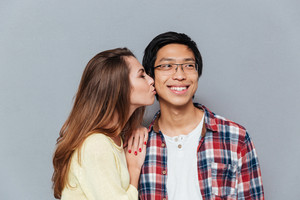 Close up portrait of a smiling young couple kissing isolated on the gray background