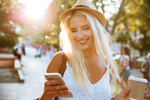 Close up portrait of a smiling young girl in hat holding take away coffee cup and typing message on smartphone outdoors