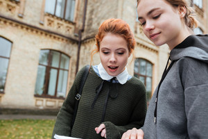Close up portrait of a two female students learning outside at the university campus
