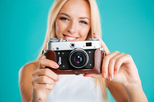 Close up portrait of a young attractive woman with retro camera isolated on the blue background
