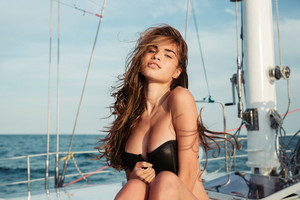 Close up portrait of a young beautiful brunette girl in swimsuit posing on the yacht