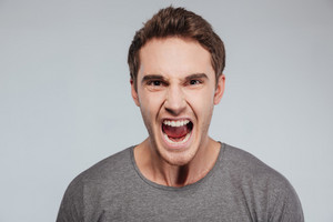 Close up portrait of a young casual man screaming at camera over white background
