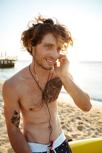 Close up portrait of a young handsome curly surfer listening music with earphones while sitting on the surfboard at the beach