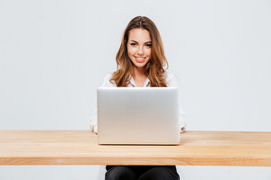 Close up portrait of an attractive smiling businesswoman using laptop while sitting at the office desk over white background
