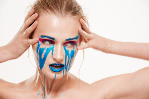Close up portrait of beautiful girl with blue tears. Hands near face. Color make up