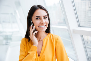 Close up portrait of Business woman in orange shirt standing near the window and talking at phone in office. As well as woman looking at camera