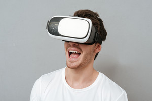 Close up portrait of Happy man in virtual reality device in studio. Isolated gray background