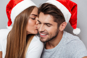 Close up portrait of kissing couple in christmas hats. Gray background