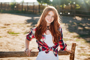 Close up portrait of pretty smiling redhead cowgirl leaning on the ranch fence