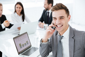 Close up Portrait of smiling business man sitting by the table with colleagues and talking at phone in office