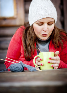 Close up portrait of winter girl knitting and drinking hot drink
