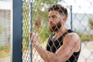 Close up portrait of young bearded man looking through metal urban fence outdoors