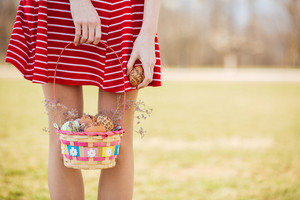 Close up portrait of young girl standing and holding basket with painted easter eggs outdoors