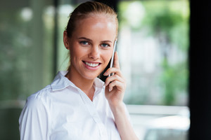 Close up potrait if a smiling businesswoman talking on the phone and looking at camera