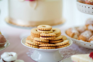 Close up, sandwich cookies filled with jam on ceramic cakestand. Studio shot.