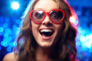 Close-up shot of a cheerful or surprised girl wearing heart-shaped sunglasses