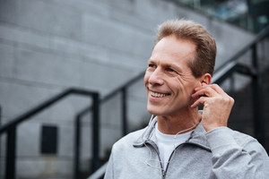 Close up smiling runner in gray sportswear with headphone standing on stairs and looking away