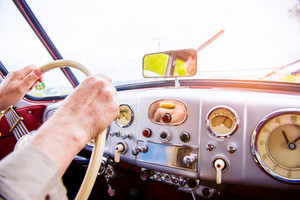 Close up unrecognizable man driving a veteran car, hands on steering wheel