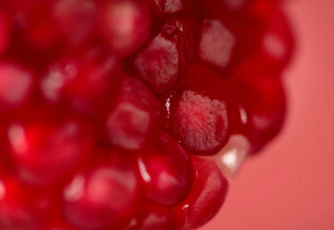 Close up view of pomegranate seeds isolated on red background