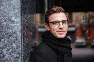 Close up young business man in glasses and warm clothes near the building