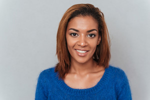 Close up young smiling african woman in sweater standing in studio. Isolated gray background
