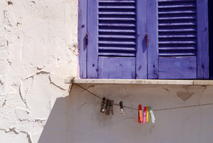 Closed blue window shutters and clothes pins on rope