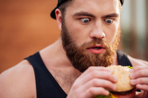 Closeup of amazed shocked bearded young man holding and looking at hamburger outdoors