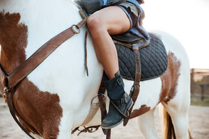 Closeup of attractive slim young woman cowgirl riding on horse outdoors