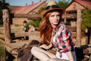 Closeup of beautiful redhead young woman cowgirl in hat