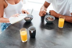 Closeup of beautiful young couple eating cereals with milk for breakfast on the kitchen